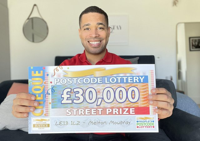People's Postcode Lottery ambassador Danyl Johnson with one of the £30,000 cheques won by three Melton residents EMN-210321-170744001